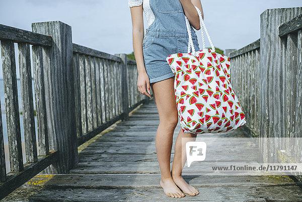 Frau stehend auf Promenade mit Strandtasche  Teilansicht