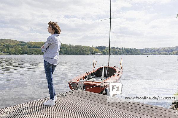 Frau am Steg stehend mit festgemachtem Segelboot