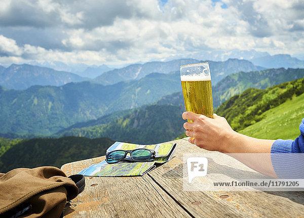 Deutschland  Chiemgau  Hand des Wanderers auf dem Hochfelln mit Bierglas  Teilansicht