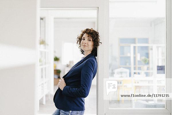 Geschäftsfrau steht in ihrem Büro und lehnt sich in den Türrahmen.