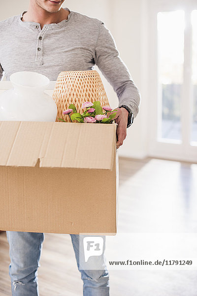 Junger Mann mit Karton in neuem Zuhause