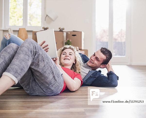 Glückliches junges Paar in neuem Zuhause auf dem Boden liegend mit Tablette