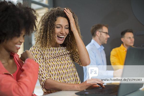 Zwei glückliche Frauen im Büro teilen sich einen Laptop