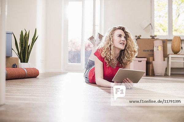 Junge Frau in neuem Zuhause auf dem Boden liegend mit Tablette
