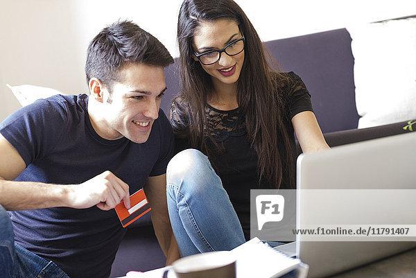 Junges Paar mit Kreditkarte mit Laptop im Wohnzimmer