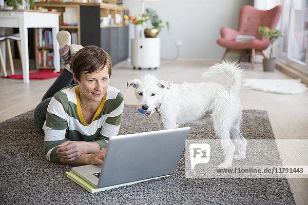 Frau auf dem Boden liegend in ihrer Wohnung mit Blick auf Laptop
