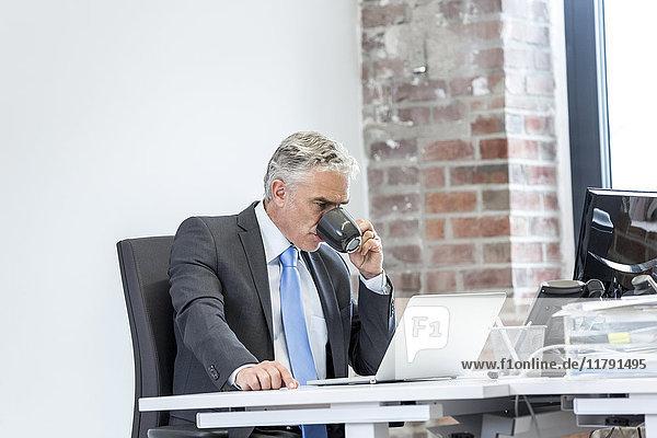 Ein reifer Geschäftsmann  der im Büro sitzt und Kaffee trinkt.