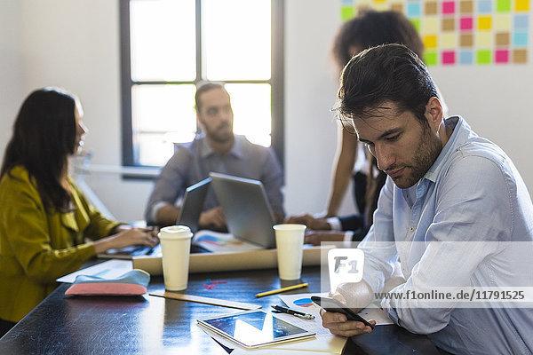 Geschäftsmann überprüft Handy während einer Besprechung im Büro