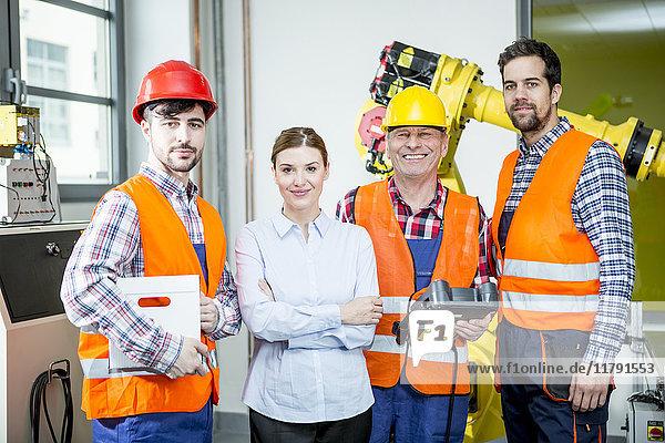 Porträt der selbstbewussten Mitarbeiter in der Fabrik mit Industrieroboter im Hintergrund