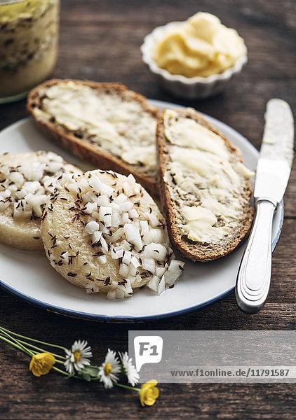 Scheiben Roggenbrot  Harzer Roller Käse mit Zwiebeln und Kümmel auf dem Teller