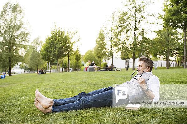 Erwachsener Geschäftsmann im Stadtpark auf Gras liegend