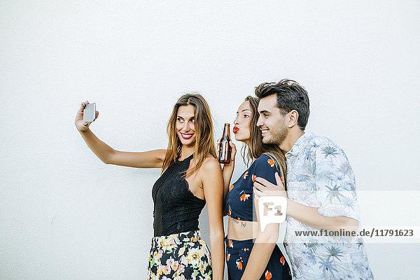 Freunde  die einen Selfie mit Smartphone vor der weißen Wand nehmen