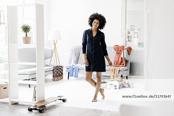 Hübsche junge Frau  die in ihrem Wohnzimmer steht.