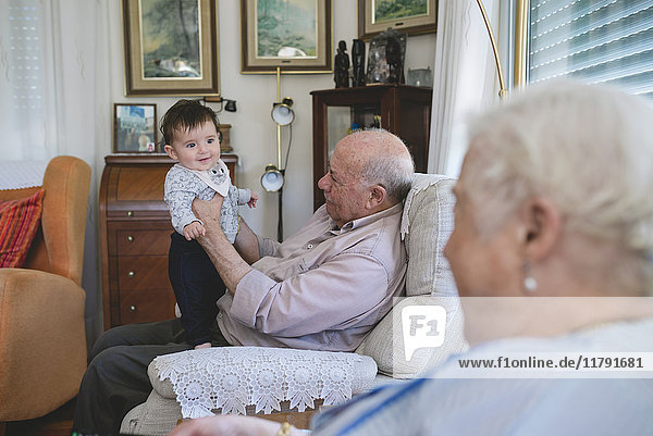 Happy Baby Mädchen stehend mit Hilfe von Urgroßvater zu Hause