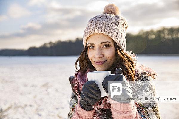 Porträt einer lächelnden Frau  die im Winter ein heißes Getränk aus einer Tasse im Freien trinkt.