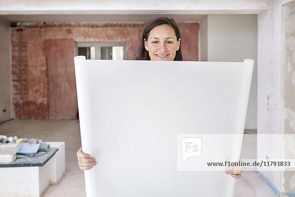 Lächelnde Frau in der leeren Wohnung mit Plan