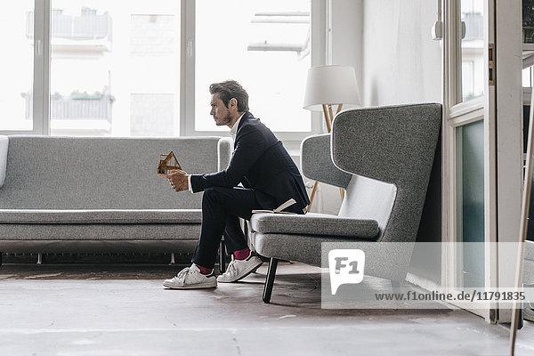 Architekt auf Sofa mit Architekturmodell