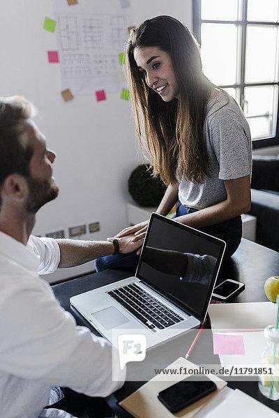 Liebespaar mit Laptop zu Hause beim Reden