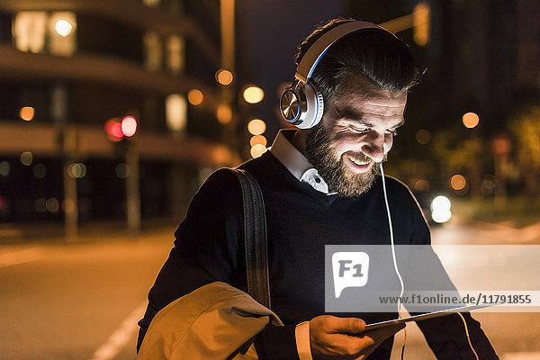 Lächelnder junger Mann mit Tablett und Kopfhörer in der Stadt bei Nacht