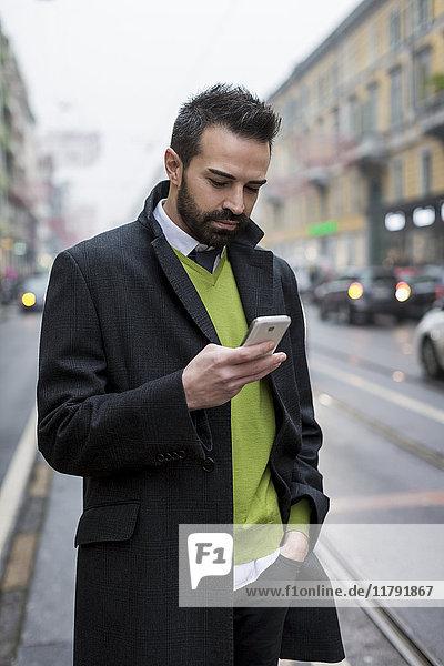 Geschäftsmann in der Stadt überprüft Handy