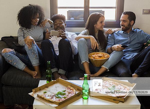 Glückliche Freunde  die sich auf dem Sofa treffen.