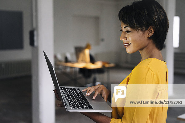 Smiling woman using laptop in empty office