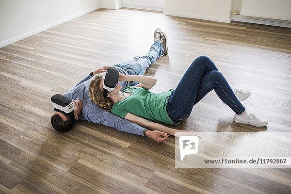 Junges Paar auf dem Boden liegend in leerer Wohnung mit VR-Brille
