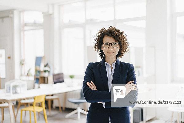 Geschäftsfrau steht in ihrem Büro mit gekreuzten Armen