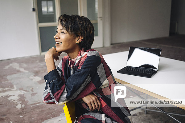 Lächelnde Frau sitzt auf dem Stuhl mit Laptop auf dem Tisch