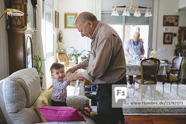 Urgroßvater  der sich zu Hause um ein kleines Mädchen kümmert.