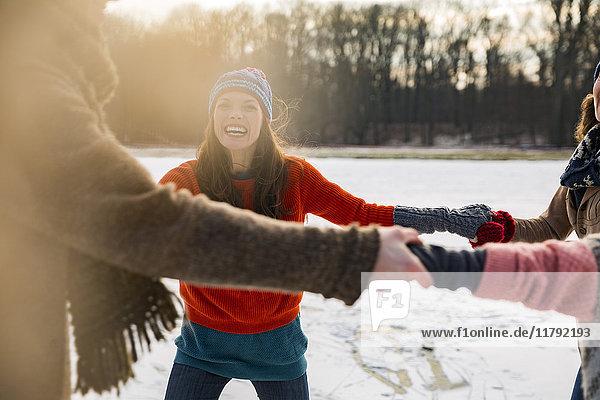 Freunde Eislaufen im Kreis auf dem zugefrorenen See