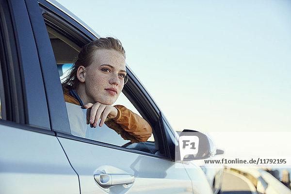 Junge Frau  die aus dem Auto schaut