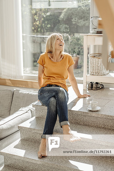 Happy woman sitting on stairs at home