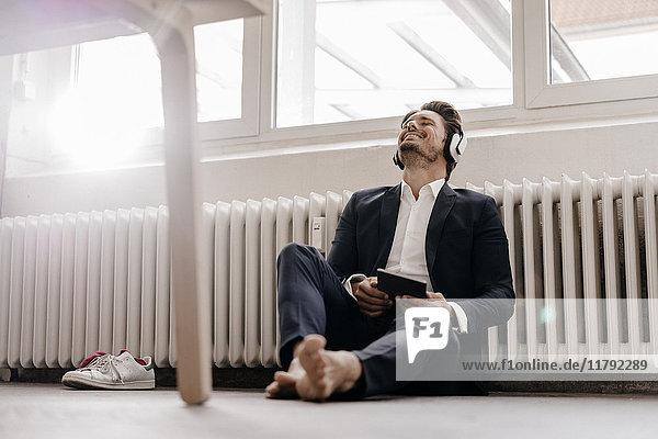 Geschäftsmann mit Tablett und Kopfhörer auf dem Boden sitzend