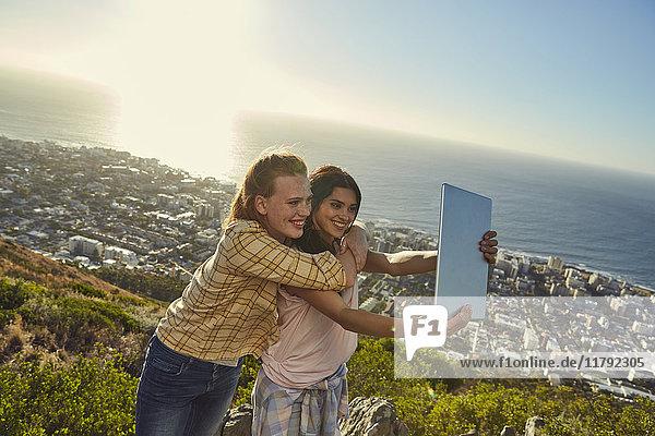 Südafrika  Kapstadt  Signal Hill  zwei junge Frauen über der Stadt  die einen Selfie mit Tablette nehmen.