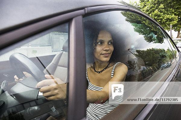 Frau  die ein Auto fährt und aus einem Autofenster schaut.