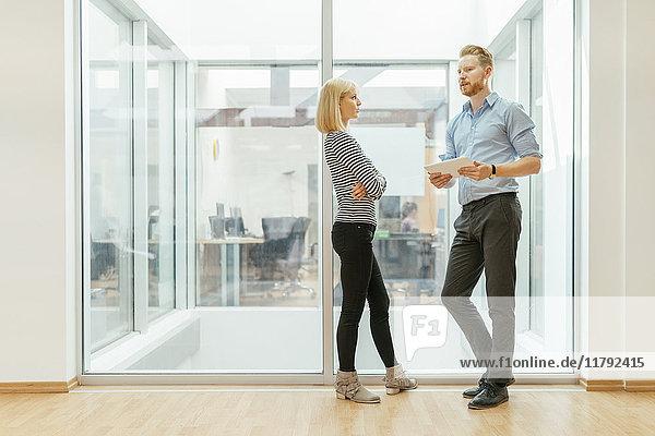 Geschäftsmann und Frau im Flur stehend  sprechend