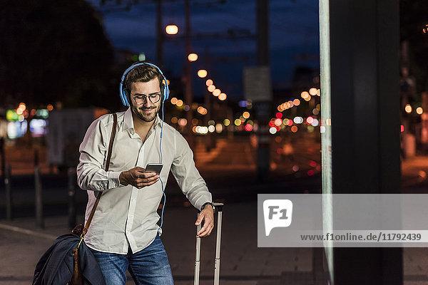 Junger Mann in der Stadt mit Kopfhörer und Handy bei Nacht