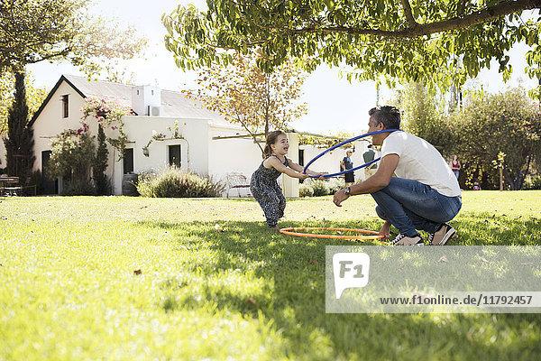 Vater spielt mit Tochter im Gras