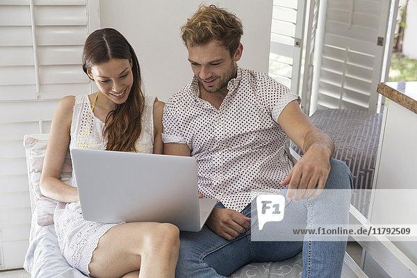 Lächelndes junges Paar teilt Laptop