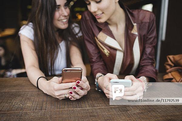 Zwei junge Frauen  die Handys in einer Bar benutzen.