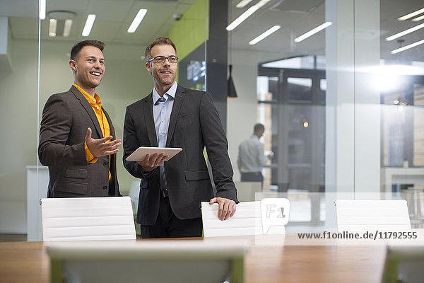 Zwei Geschäftsleute mit Tablette im Vorstandszimmer