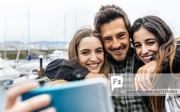 Drei Freunde,  die einen Selfie am Yachthafen nehmen.
