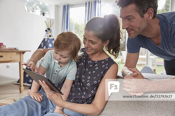 Glückliche Familie mit Tablette zu Hause
