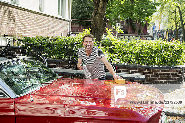 Smiling mature man washing his sports car