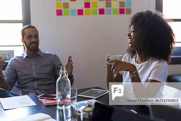 Fröhliche Geschäftsfrau beim Kaffeetrinken während eines Meetings im Büro