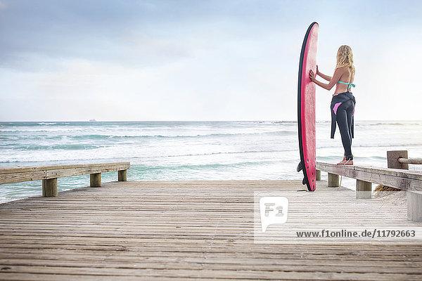 Frau am Meer mit Surfbrett
