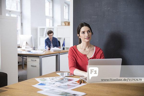 Frau mit Laptop auf dem Tisch im Büro denken