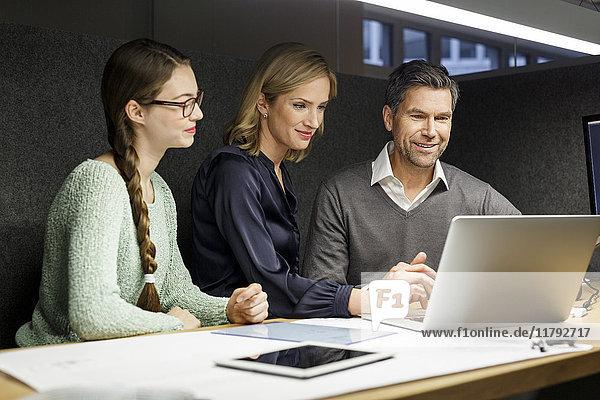 Kollegen teilen Laptop in der Meeting-Box