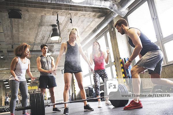 Gruppe von jungen Leuten  die Frauen beim Gewichtheben im Fitnessstudio anfeuern.